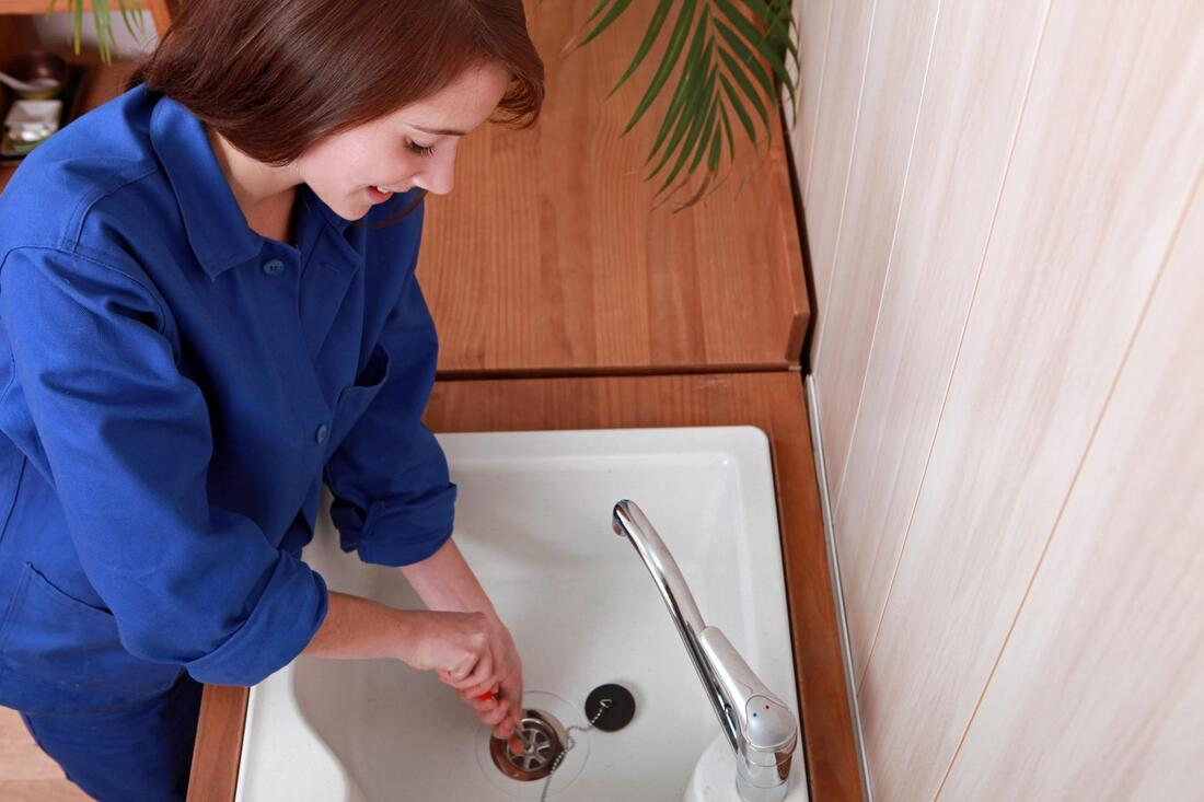 a lady plumber unblocking the drain