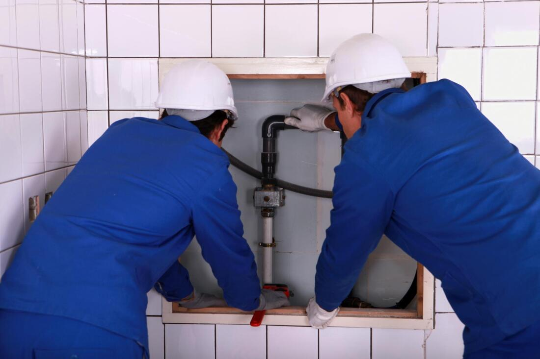 two male plumbers are helping each other
