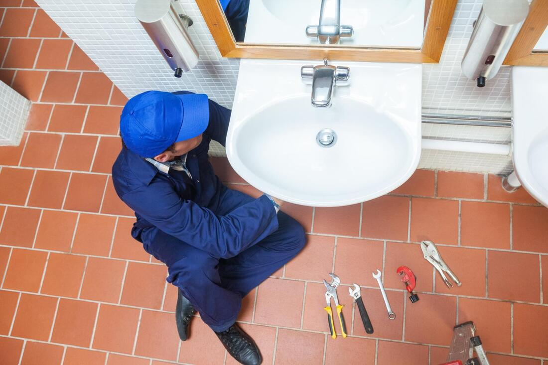 plumber sitting down to fix the sink